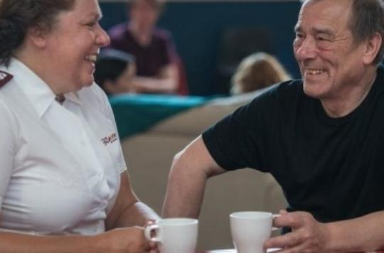 Man chatting to salvationist over tea