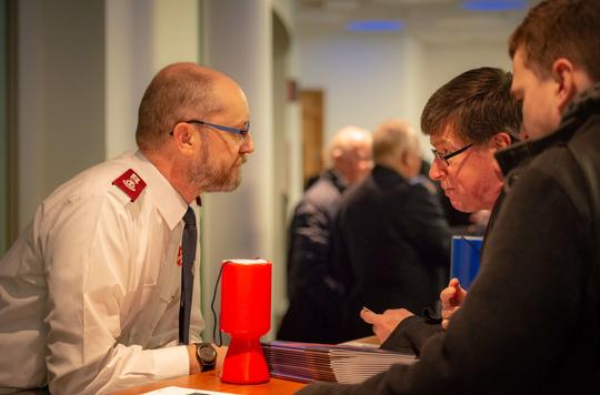 Salvation Army Officer leans helpfully over desk