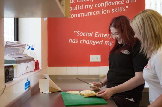 Woman making sandwiches in front of social enterprise endorsement quotes