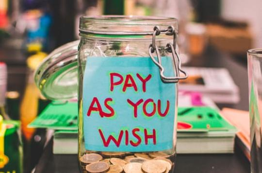 Jar full of change and a PAY AS YOU WISH message written on a piece of paper in red felt tip