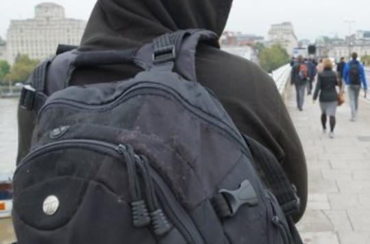 Hooded person wearing backpack