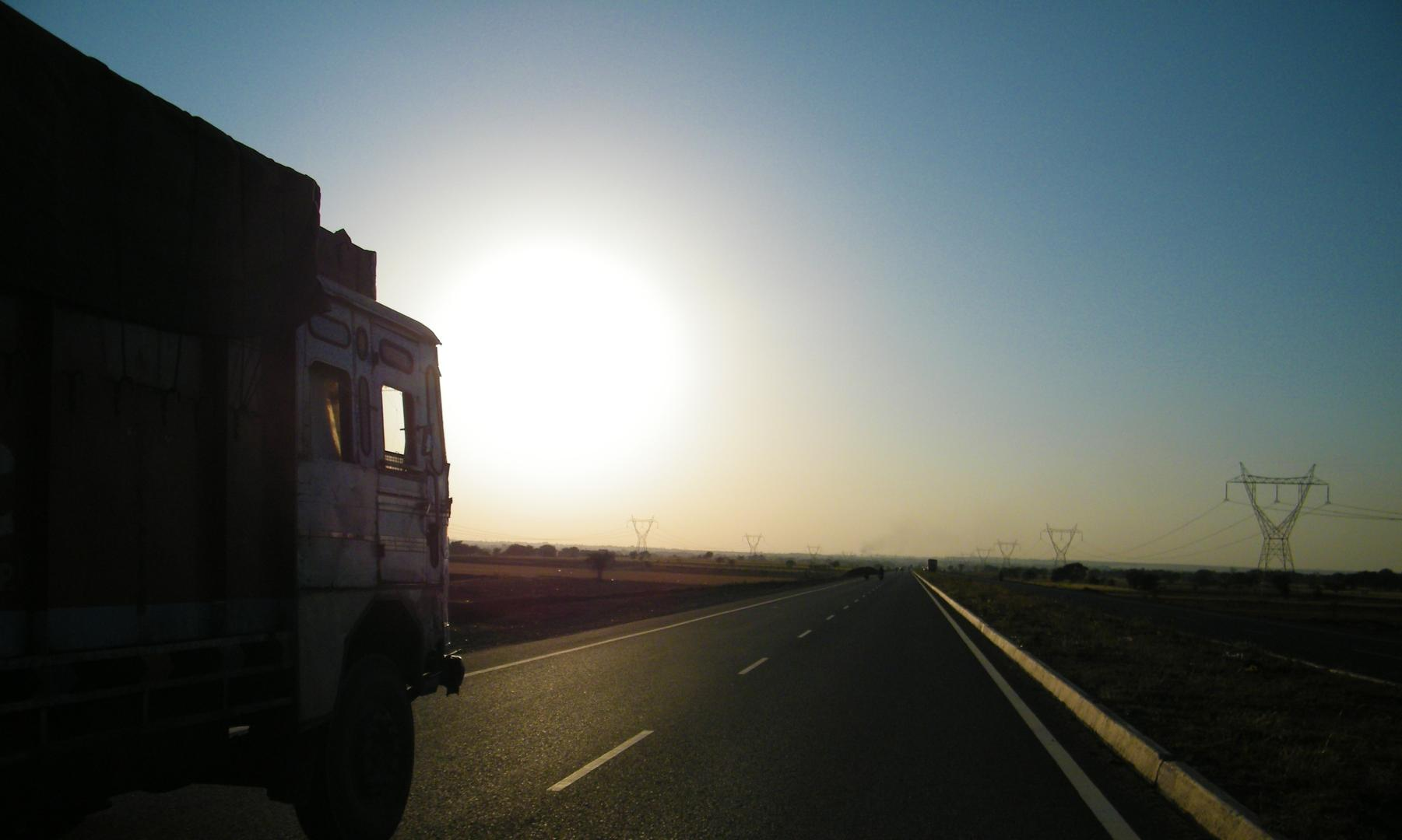 Lorry driving into either sunset or sunrise