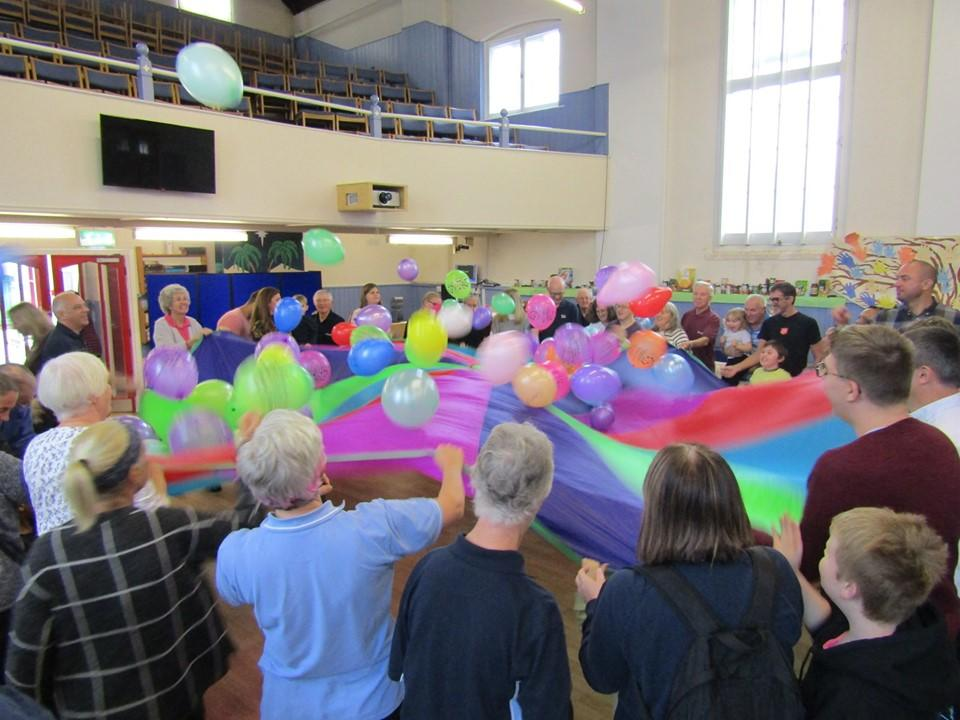 Our vibrant church goers all holding edges of a parachute bouncing balloons above head height