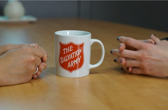 A mug with a Salvation Army logo in between two people's closed hands on a table