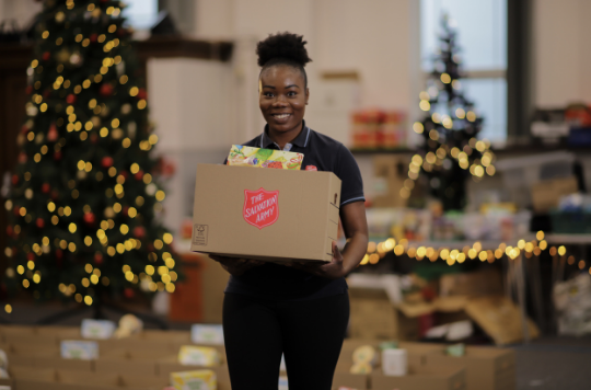 Salvation Army volunteer carrying a Christmas hamper