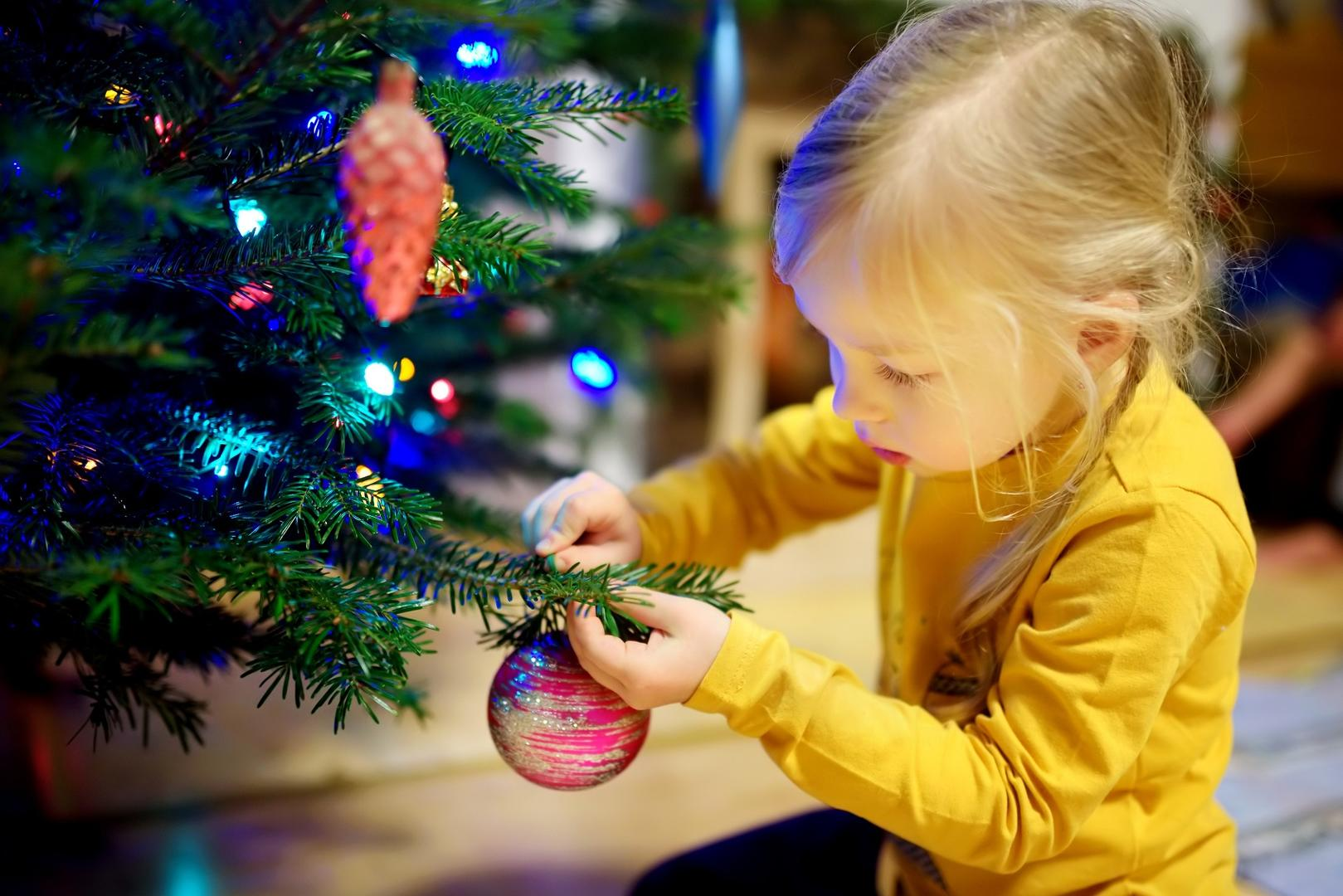 Little girl by Christmas tree