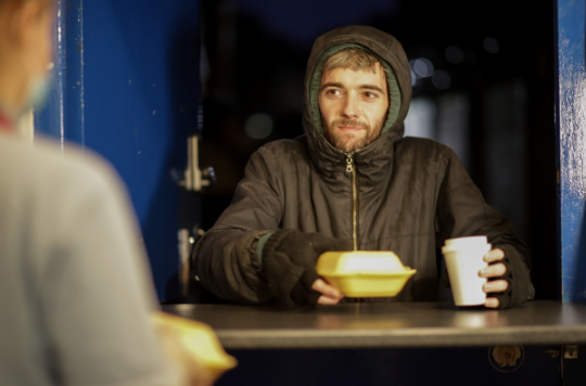 A rough sleeper receives hot food and drink