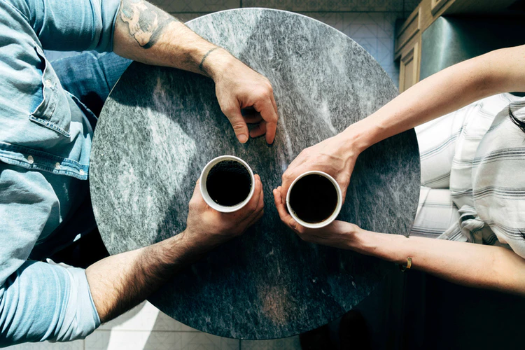 Two people holding coffee having a conversation